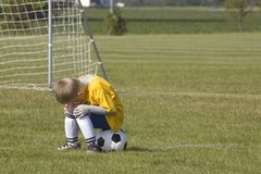 Sad Soccer player. Here is a photo of a young boy sitting on a soccer ball.  He is saddened because his team just lost the game Stock Images