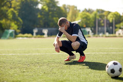 Sad soccer player with ball on football field. Sport, football, fail, loss and people - sad soccer player with ball on field Royalty Free Stock Photography