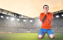 Sad soccer player. Unhappy soccer or football player kneeled down with hands on his face at stadium Stock Photos