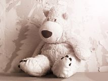 A sad soft toy bear in the old room. Black and white royalty free stock photo