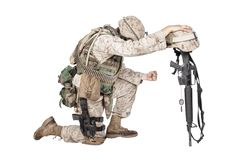 Sad soldier kneeling because of friend death royalty free stock photo