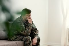 Sad soldier in uniform covering his mouth while sitting on a sofa stock image