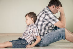 Sad son and his dad sitting on the floor at room at the day time Stock Images