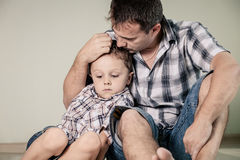 Sad son and his dad sitting on the floor at room at the day time Royalty Free Stock Images