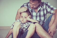 Sad son and his dad sitting on the floor at room at the day time Royalty Free Stock Photos