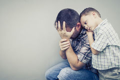 Sad son hugging his dad Stock Image