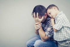 Sad son hugging his dad Stock Image