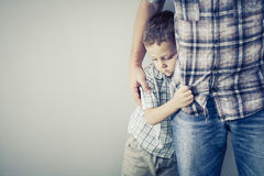 Sad son hugging his dad. Near wall at the day time Stock Image