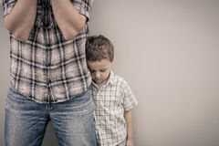 Sad son hugging his dad near wall Stock Images