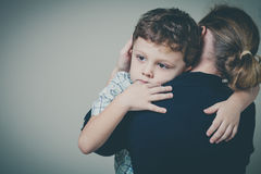 Sad son hugging his mother. At home. Concept of couple family is in sorrow royalty free stock photo