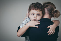 Sad son hugging his mother at home. Concept of couple family is in sorrow stock images