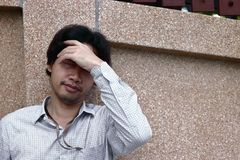 Sad and stressed Asian business man with hands on forehead leaning on the wall Royalty Free Stock Photos