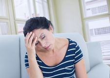 Sad stressed woman on couch by windows Stock Image