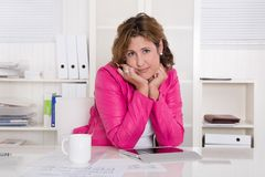 Sad and stressed woman sitting frustrated at desk. Royalty Free Stock Photos