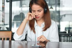 Sad stressed young Asian woman listening music with headphones in living room stock images