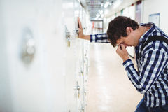 Sad student leaning on locker Stock Images