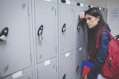 Sad student leaning on locker Royalty Free Stock Photo