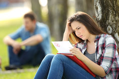 Sad student looking at failed exam. Single sad student looking at failed exam sitting on the grass in a park with unfocused people in the background stock photo