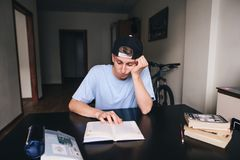 A sad student is reluctant to read a book in his room. Doing homework. Teaching at home.  Royalty Free Stock Photo