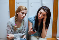 Sad student showing a text message to her friend stock photos
