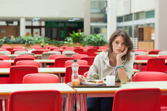 Sad student sitting in the cafeteria with food tray Royalty Free Stock Photos