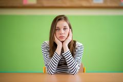 Sad student sitting in classroom with her head in hands. Education, high school, bullying, pressure, depression. Sad student sitting in classroom with her head Royalty Free Stock Image