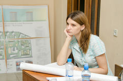 Sad student sitting at desk with drawings Stock Photography