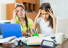 Sad students studying at home. Portrait of two tired girls sitting at the table with laptops and books. Selective focus Royalty Free Stock Images