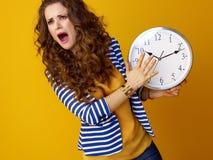 Sad stylish woman on yellow background with clock Stock Image