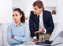 Sad subordinate woman being accused to making mistake by man col. Dreary  subordinate women being accused to making mistake by men colleague in company office Stock Image