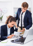 Sad subordinate woman being accused to making mistake by man col. Sad subordinate women being accused to making mistake by men colleague in company office Stock Images
