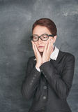 Sad teacher. On the school blackboard background royalty free stock images
