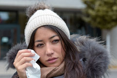 Sad tearful woman holding a handkerchief. Sad tearful woman in warm winter fashion holding a handkerchief to her face to dry the tears from her eyes looking to Royalty Free Stock Images