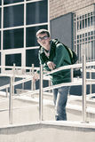 Sad teen boy with backpack against a school building Stock Images