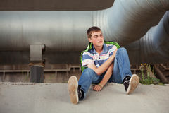 Sad teen boy in depression sitting on the ground Royalty Free Stock Photos
