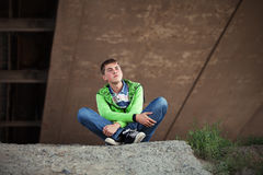 Sad teen boy in depression sitting on the ground Royalty Free Stock Photography
