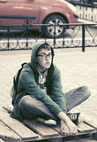 Sad teen boy in depression sitting on sidewalk. In city street Royalty Free Stock Photography