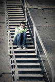Sad teen boy in depression sitting on steps Stock Photos