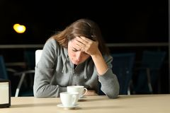 Sad teen complaining after break up. In a restaurant in the night royalty free stock photo
