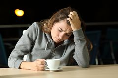 Sad teen complaining in a coffee shop in the night. Portrait of a sad teen complaining alone in a coffee shop in the night Stock Photos