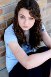 Sad teen girl. Headshot of sad teen girl seated against a brick wall royalty free stock photography
