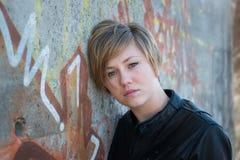 Sad teen girl. Sad, beautiful teen girl rests head on cement, graffiti wall Stock Photos