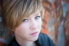 Sad teen girl. Sad, beautiful teen girl rests head on cement, graffiti wall Royalty Free Stock Photography