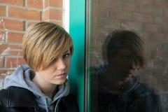 Sad teen girl. Sad, beautiful teen girl rests head on cement, graffiti wall royalty free stock photos