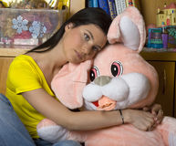 Sad teen girl with bunny toy. Sad teen girl huging bunny toy royalty free stock photography