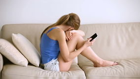 Sad teen girl checking phone and crying sitting on couch