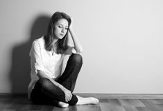 Sad teen girl at floor near wall. Royalty Free Stock Photography