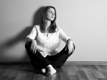 Sad teen girl at floor near wall. Royalty Free Stock Photo