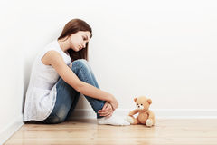 Sad teen girl on floor. With toy Stock Images