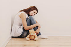 Sad teen girl on floor. With toy Royalty Free Stock Photography